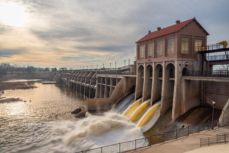 Late afternoon photo of dam with water flowing out of the gates