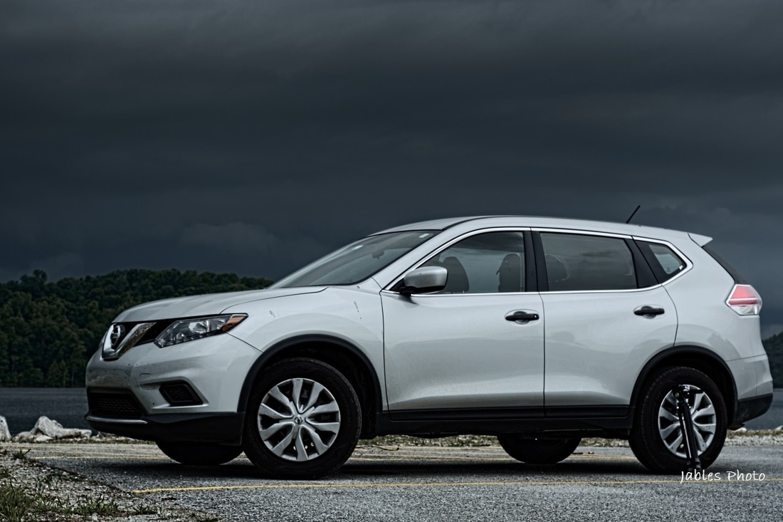 2016 Nissan Rogue parked near Beaver Lake dam with storm in background